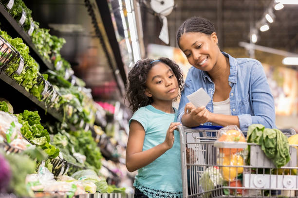 mother and daughter grocery shop together using list - shopping stock photos and pictures