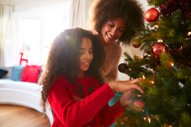 Mother And Daughter Hanging Decorations On Christmas Tree At Home Mother And Daughter Hanging Decorations On Christmas Tree At Home christmas family stock pictures, royalty-free photos & images