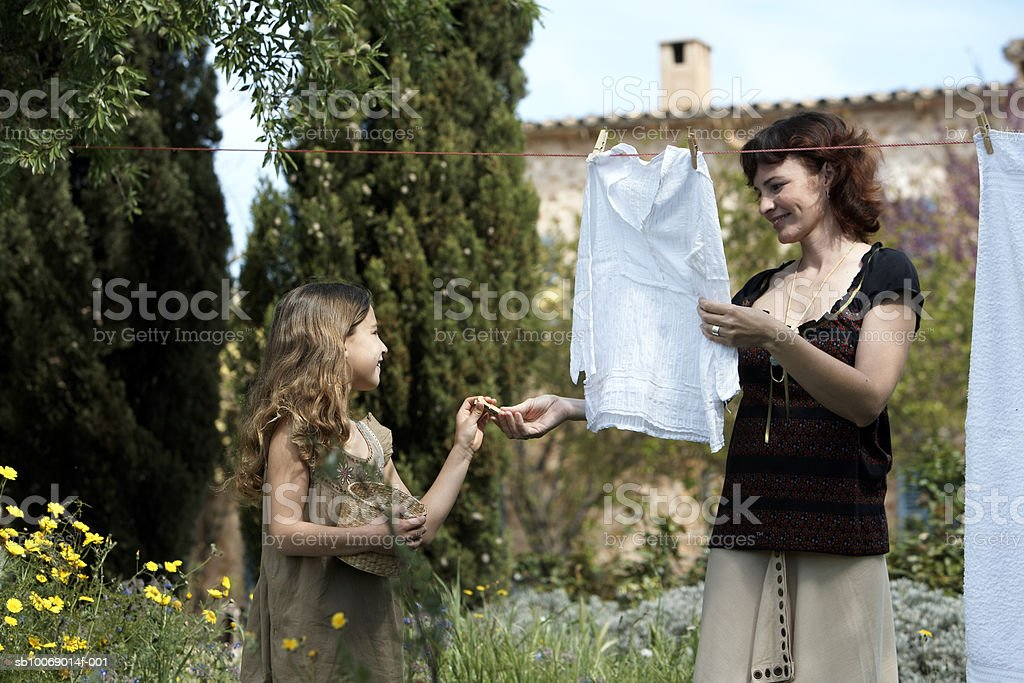 Mother and daughter (8-9) hanging laundry in garden 免版稅 stock photo