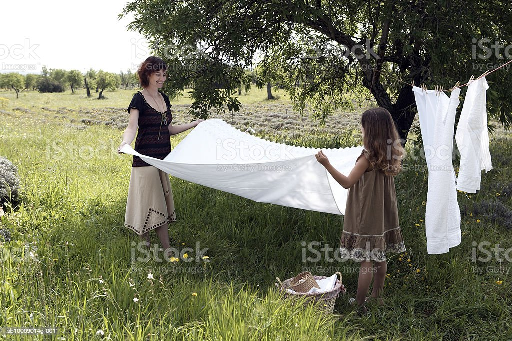 Mother and daughter (8-9) hanging laundry in garden royalty-free stock photo