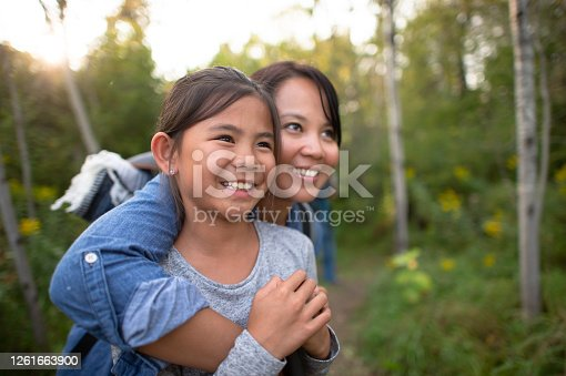 A woman hugs her daughter and they both smile while standing in a beautiful forest.