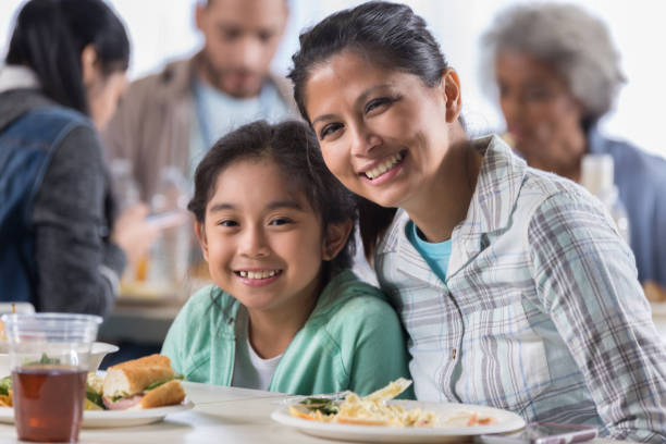 Mother and daughter have lunch in soup kitchen Mid adult woman and her elementary age daughter have lunch in a soup kitchen. People and volunteers are in the background. filipino ethnicity stock pictures, royalty-free photos & images