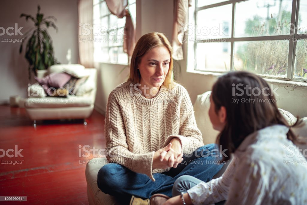 Mother and daughter having a talk. Mother and daughter at home having a  talk at home 12-13 Years Stock Photo