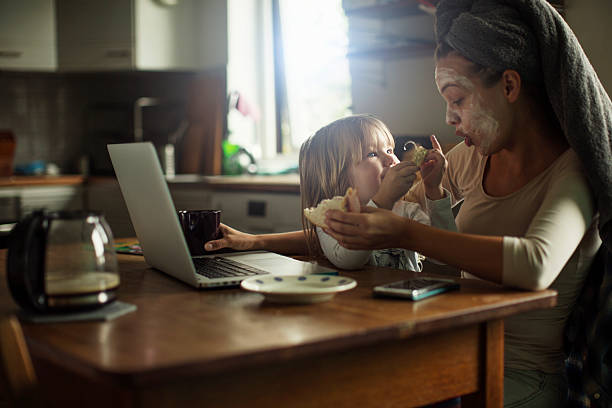 Mother and daughter having breakfast Photo of a mother and daughter having breakfast together in the kitchen multi tasking stock pictures, royalty-free photos & images