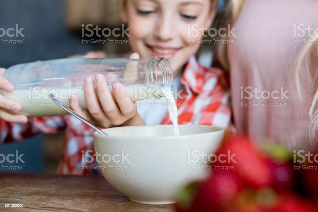 mother and daughter having breakfast stock photo