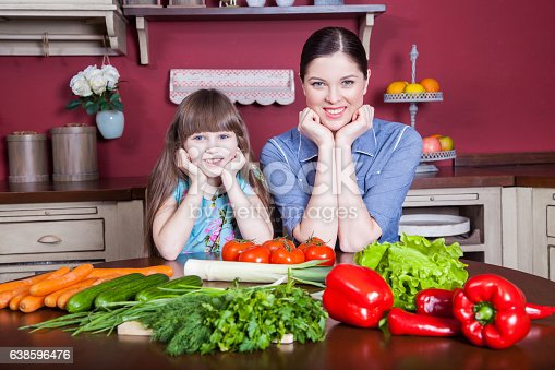 istock Mother and daughter having fun and making vegetable salad together. 638596476