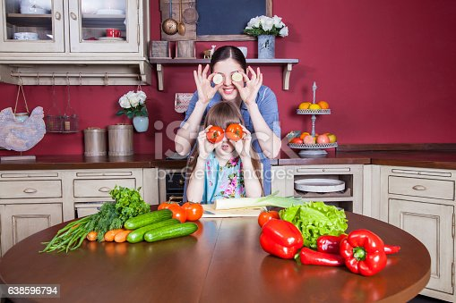istock Mother and daughter having fun and making vegetable salad together. 638596794