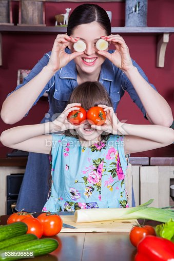 istock Mother and daughter having fun and making vegetable salad together. 638596858