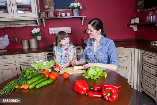 istock Mother and daughter having fun and making vegetable salad together. 638596934