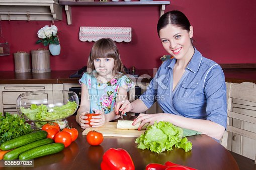 istock Mother and daughter having fun and making vegetable salad together. 638597032