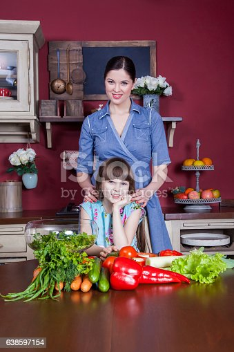 istock Mother and daughter having fun and making vegetable salad together. 638597154