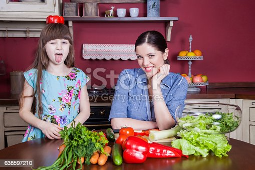 istock Mother and daughter having fun and making vegetable salad together. 638597210