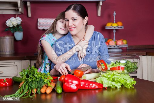istock Mother and daughter having fun and making vegetable salad together. 638597264