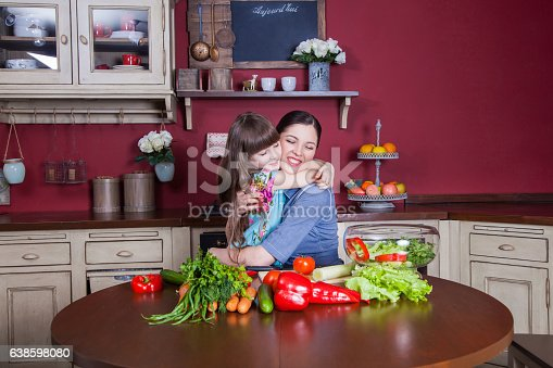 istock Mother and daughter having fun and making vegetable salad together. 638598080