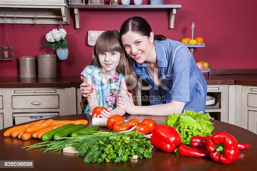 istock Mother and daughter having fun and making vegetable salad together. 638598698