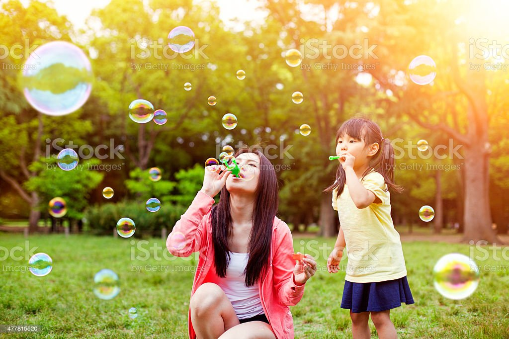 Mother and daughter having fun in park with Soap Bubbles stock photo