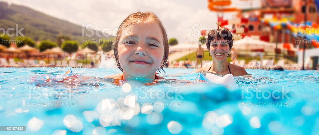 Mother and daughter having fun in pool stock photo