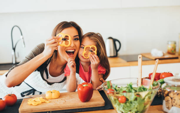 mother and daughter having fun in the kitchen - kids cooking stock photos and pictures