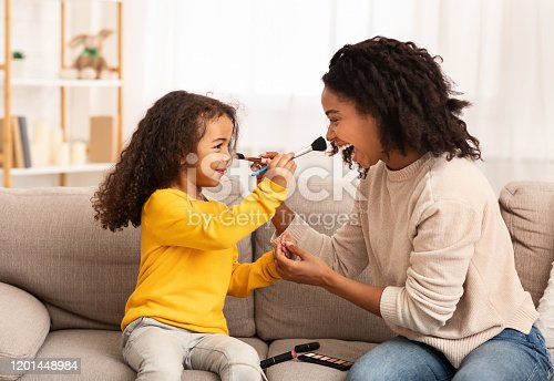 Mother And Daughter Relationship. Loving Mom And Little Kid Having Fun Making Makeup Together At Home. Selective Focus