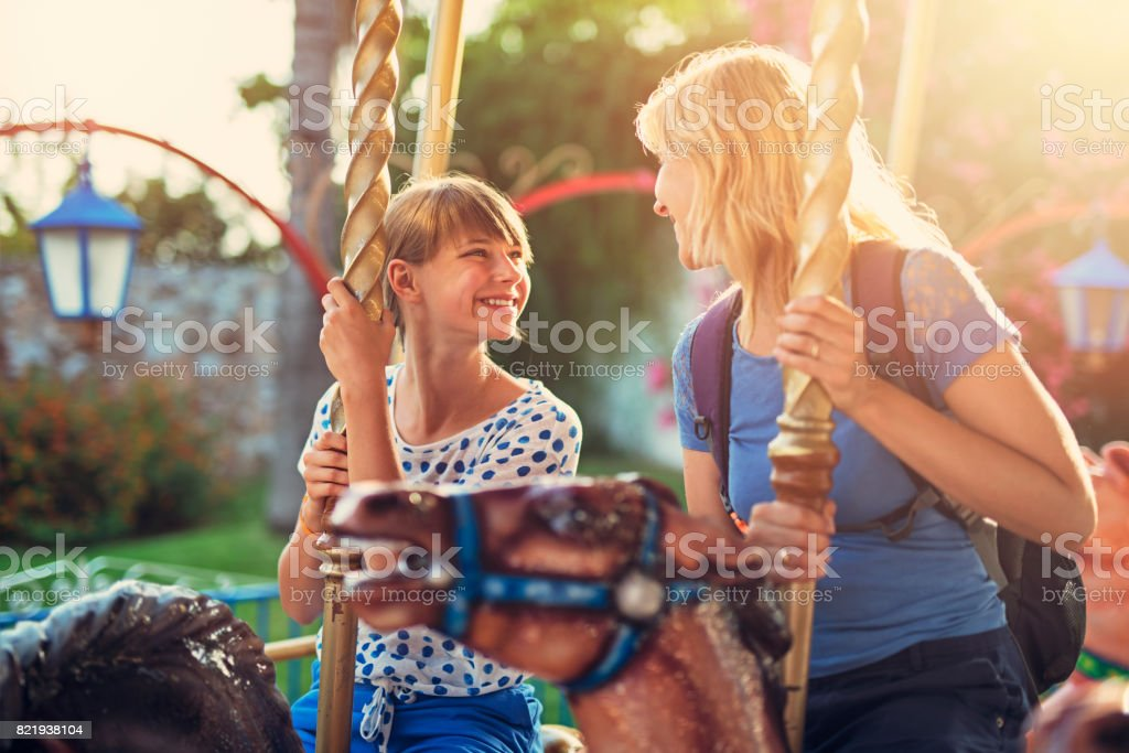 Mother and daughter having fun on carousel ride stock photo