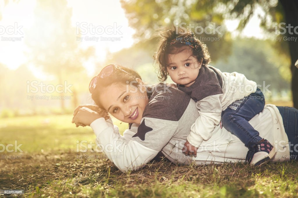 Mother and Daughter having fun on the grass in a park stock photo