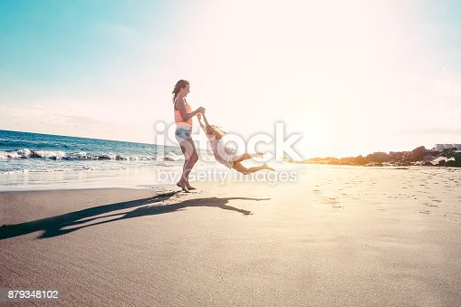 istock Mother and daughter having fun on tropical beach - Mum playing with her kid in holiday vacation next to the ocean - Family lifestyle and love concept - Sun color tones filter - Focus on silhouettes 879348102