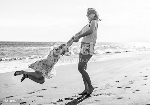 Mother and daughter having fun on tropical beach - Mum playing with her kid in holiday vacation next to the ocean - Family lifestyle and love concept - Black and white editing - Focus on baby girl