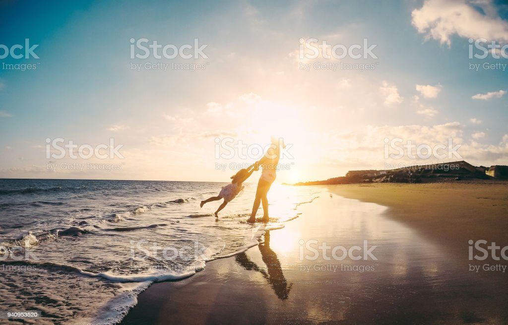 Mother and daughter having fun on tropical beach - Mum playing with her kid in holiday vacation next to the ocean - Family lifestyle and love concept - Focus on silhouettes stock photo