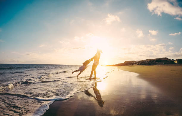 mãe e filha se divertindo na praia tropical conceito estilo de vida e o amor de família - mãe brincar com o filho em férias junto ao mar - - foco em silhuetas - viagem ao reino unido - fotografias e filmes do acervo