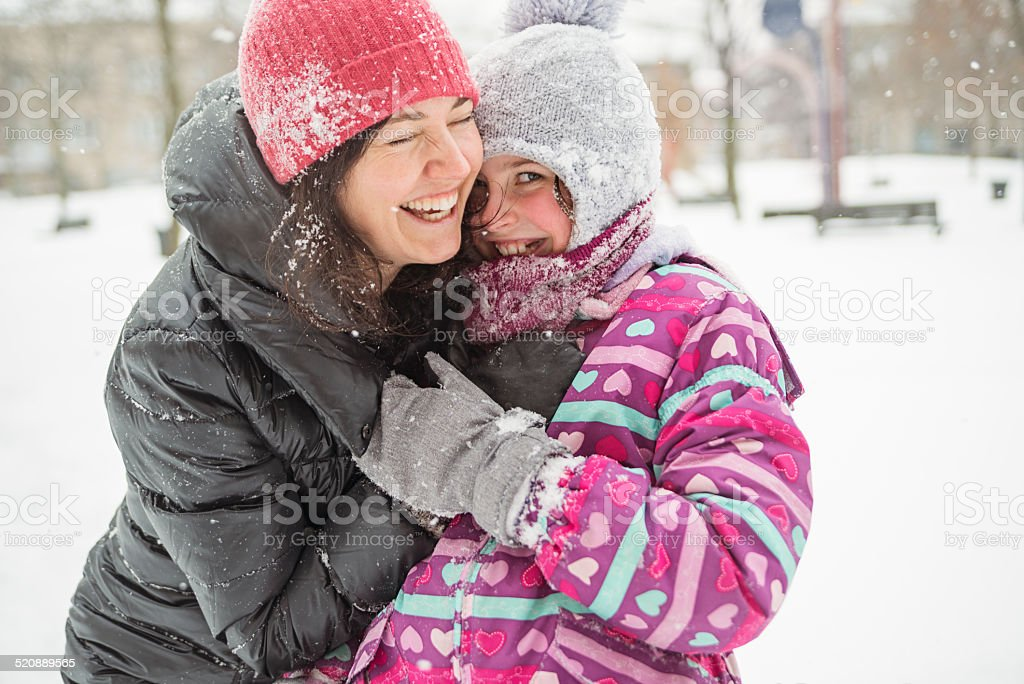Mother and daughter having fun playing in fresh fallen snow. stock photo