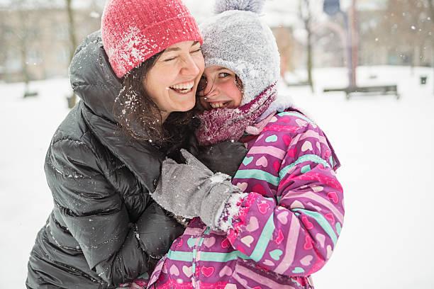 Mutter und Tochter Spaß spielen im Neuschnee. – Foto
