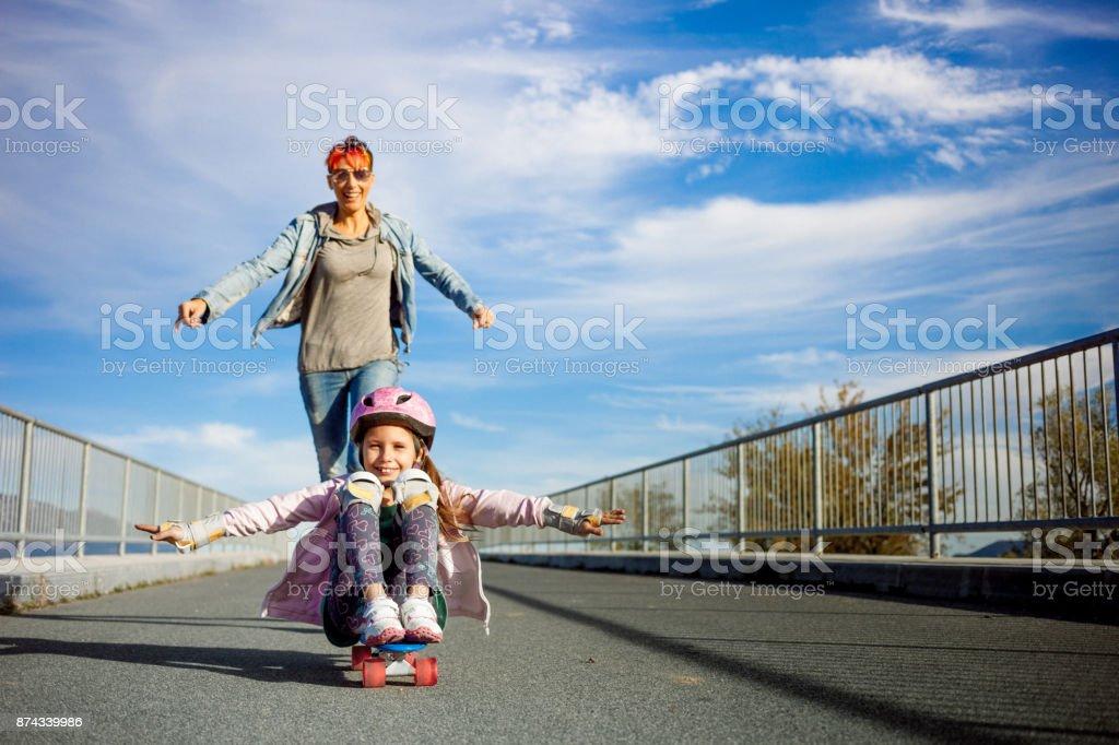 Mãe e filha tendo divertido andar skate - foto de acervo