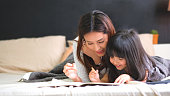 istock Mother and daughter having fun together in bedroom with teaching her to spell words and reading some hard words. 1130508150