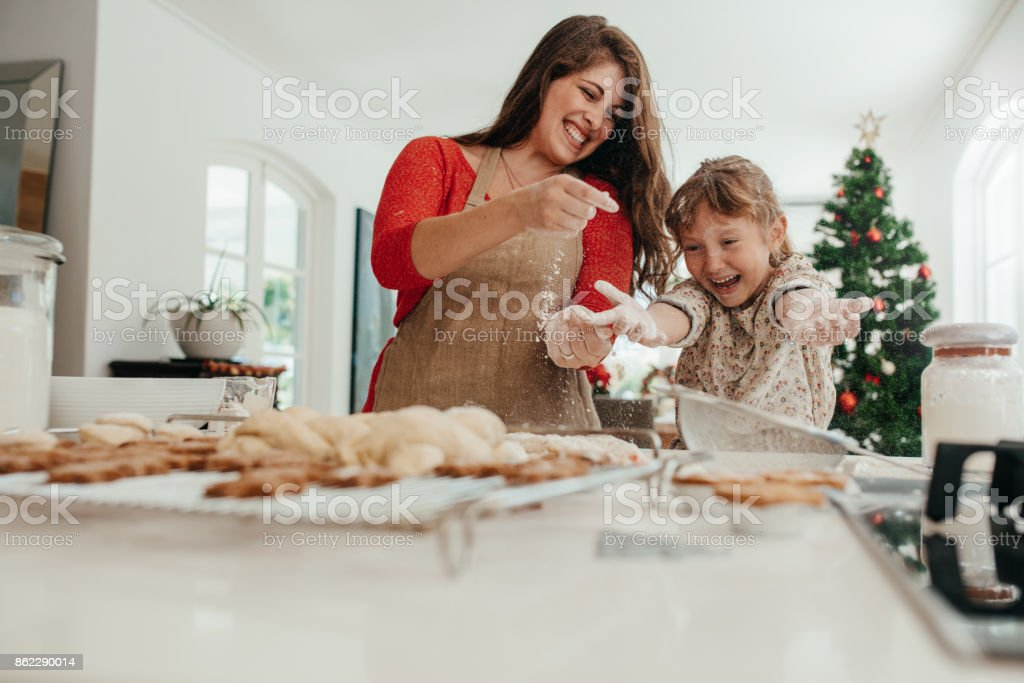 Mother and daughter having fun while making Christmas cookies. stock photo