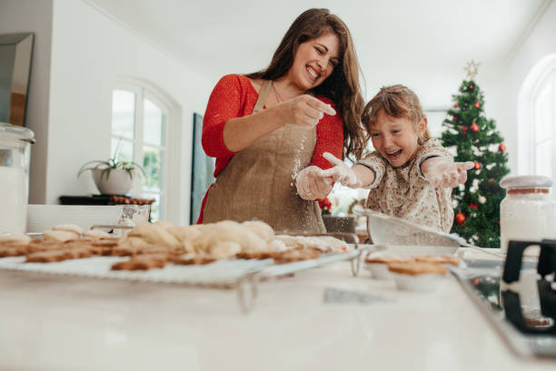 mother and daughter having fun while making christmas cookies. - christmas cooking imagens e fotografias de stock