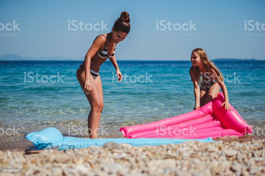 mother and daughter having fun with floating bed on the beach gm