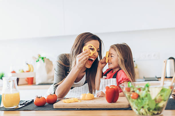 mother and daughter having fun with the vegetables - hygiène alimentaire photos et images de collection