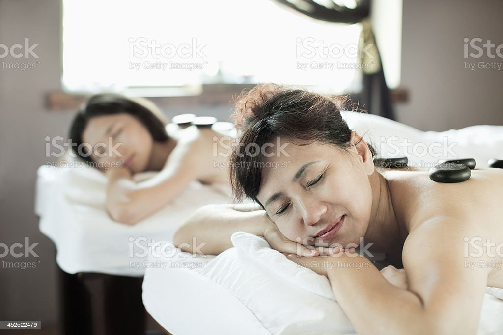Mother and Daughter Having Hot Stone Massage Together stock photo