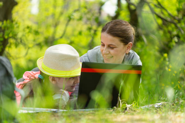 Mother and daughter having picnic in the forest. stock photo