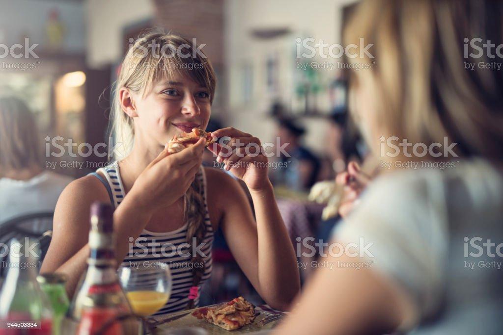 Mãe e filha comer pizza no restaurante Piza - foto de acervo