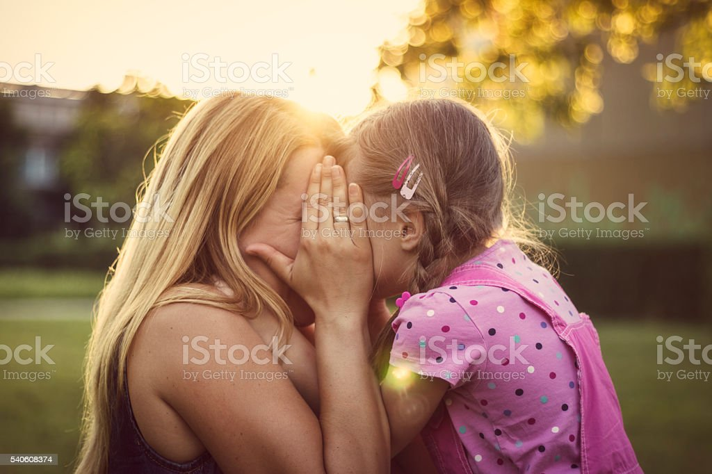 Mother and daughter hiding behind the hand stock photo