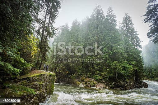 A mature Asian mother and her teenage daughter enjoy the pristine wilderness landscape of a quickly flowing river through a wooded park on a rainy, misty, autumn day from the edge of a small cliff.  Wide angle view of the Capilano River, North Vancouver, Canada.