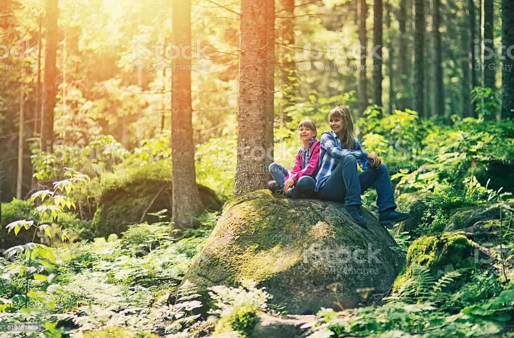 Mother and daughter hikers resting in a forest. stock photo