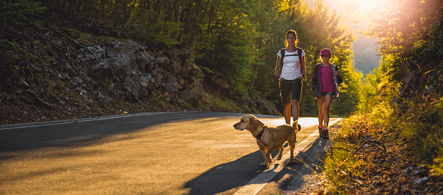istock Mother and daughter Hiking by the asphalt road 850899780