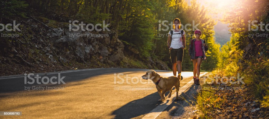 Mother and daughter Hiking by the asphalt road stock photo