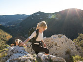 Mother and daughter hiking in mountains in sunlight