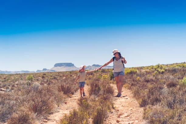 Mãe e filha caminhadas nas montanhas, estendendo as mãos - foto de acervo