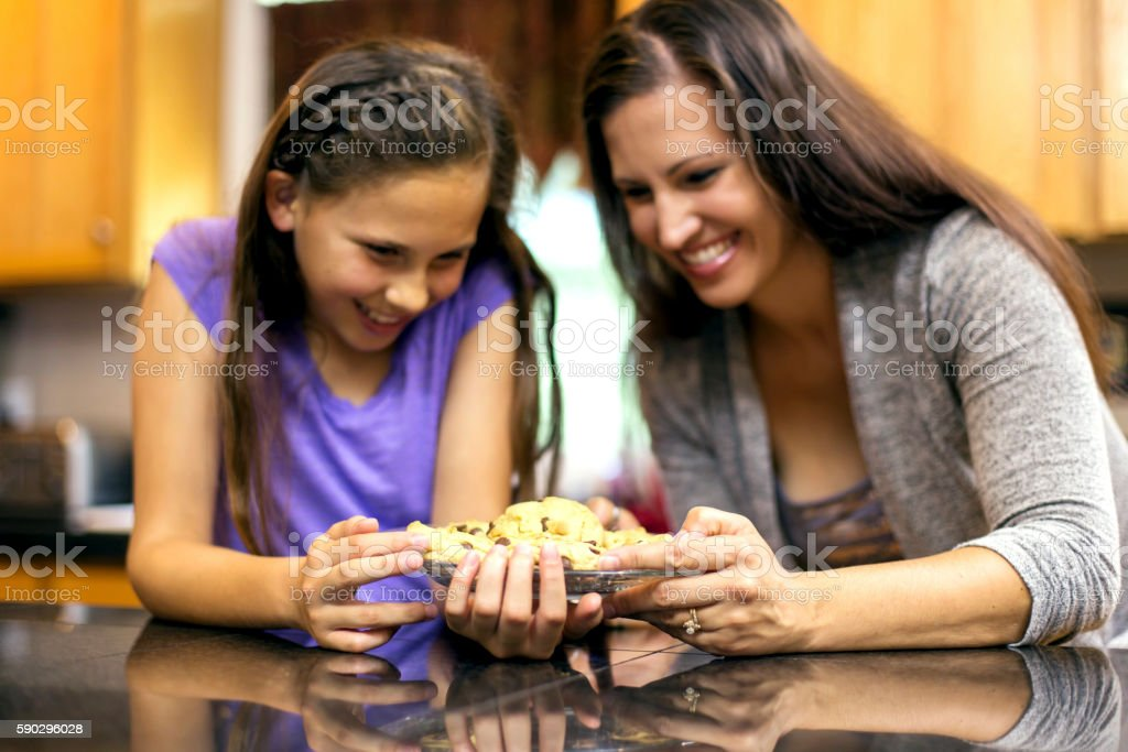 Mother and daughter holding a plate of homemade cookies royaltyfri bildbanksbilder