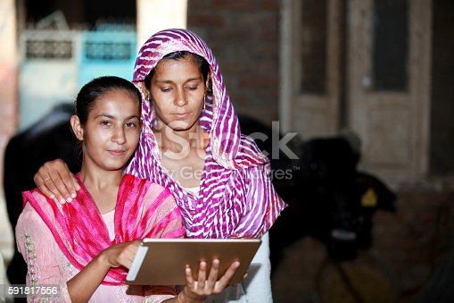 Mother And Daughter Holding Digital Tablet At Home.