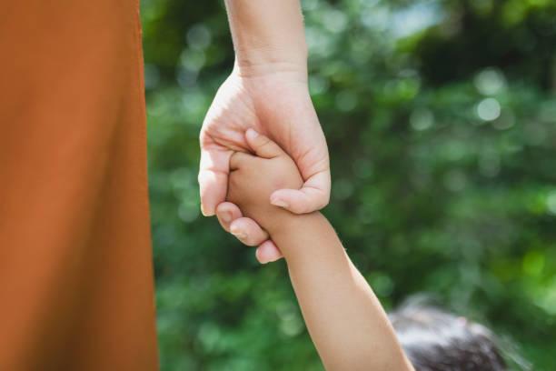 公園でお互いの手を握り合う母と娘 - 人間の手 ストックフォトと画像